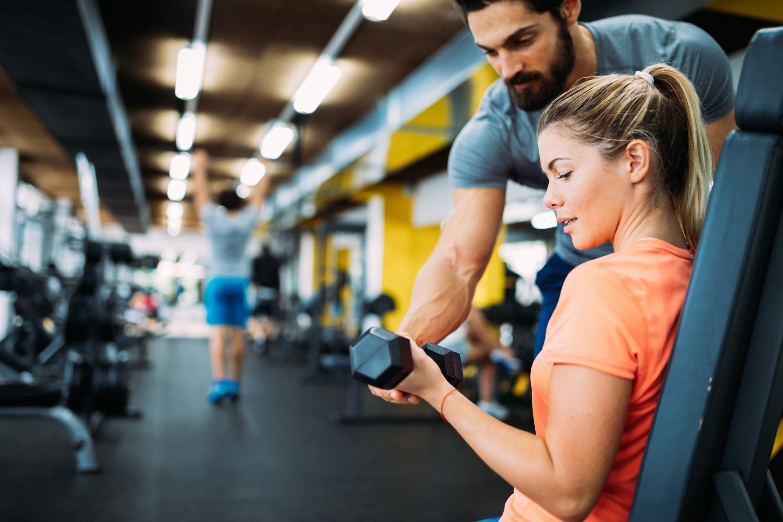 kobieta na siłowni z trenerem personalnym; jak zostać trenerem personalnym
