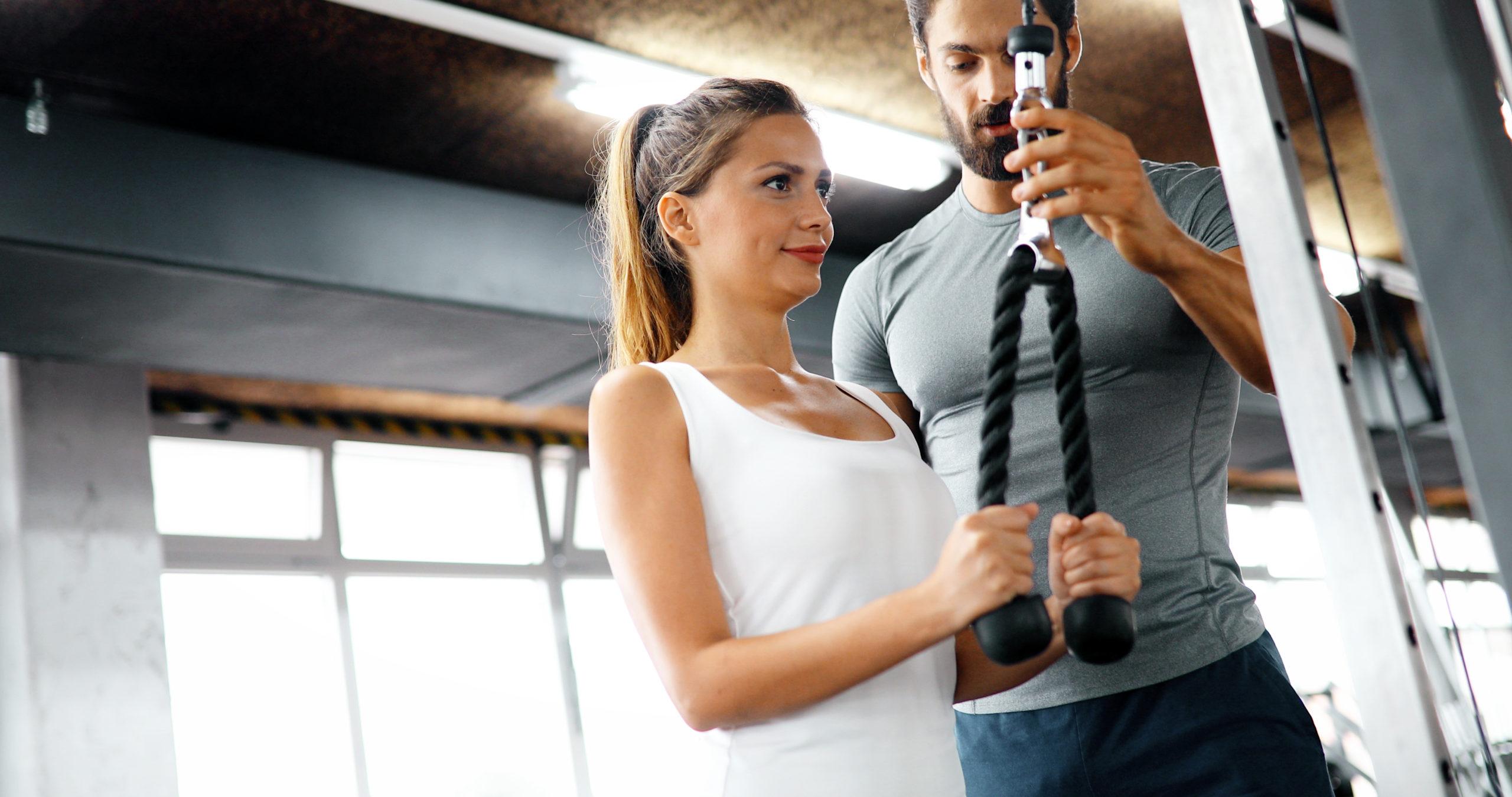 kobieta ćwiczy z trenerem personalnym; jak zostać trenerem personalnym
